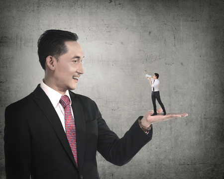 giant man: Giant business man holding little man yelling with megaphone. Politic in business Stock Photo