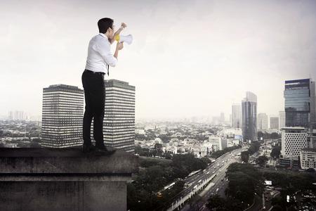 hombre de negocios que usa el megáfono hablando a la ciudad desde la azotea Foto de archivo