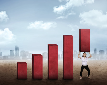 business challenge: Asian business woman lifting block of chart. Business challenge concept Stock Photo