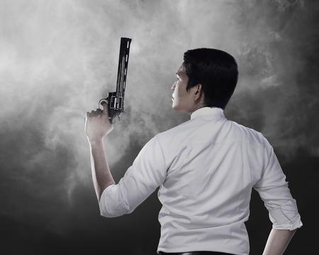 business service: Secret agent holding gun ready to fire Stock Photo