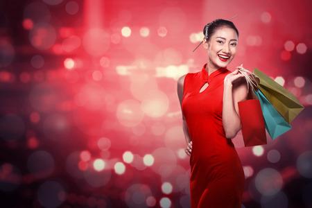 Chinese woman wearing cheongsam hold shopping bag. Happy chinese new year Stockfoto