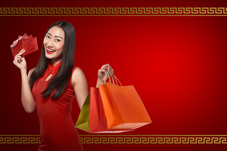 celebrate year: Asian woman in cheongsam dress, holding angpao and shopping bag. Happy chinese new year concept