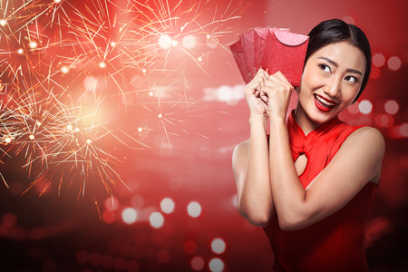 Asian woman in cheongsam dress holding angpao. Happy chinese new year concept