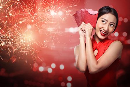 Aziatische vrouw in cheongsam jurk bedrijf angpao. Gelukkig Chinees nieuw jaar concept Stockfoto