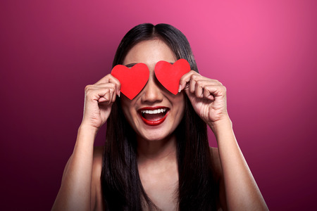 eye red: Valentine day concept. Beautiful asian girl holding red heart cover her eyes. Stock Photo
