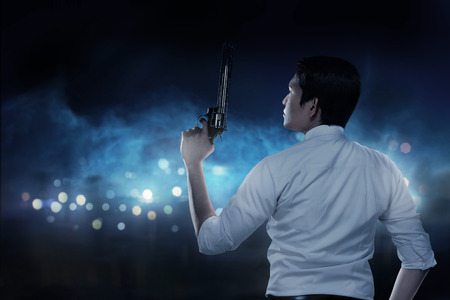 secret agent: Secret agent holding gun ready to fire Stock Photo