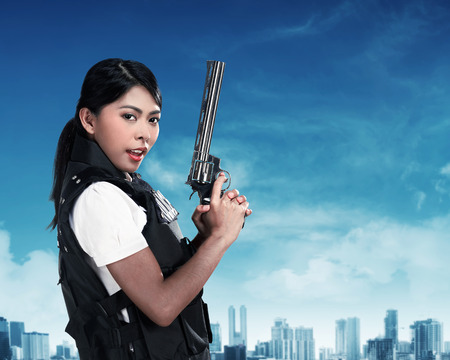 special agent: Beautiful police woman holding gun ready to fire Stock Photo