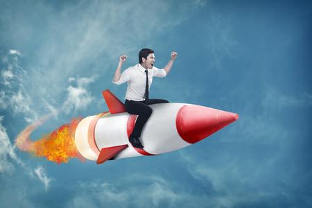 flying man: Image of asian business man flying ride rocket