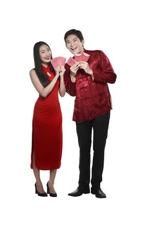 Chinese couple wear cheongsam holding angpao isolated over white background