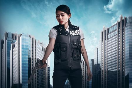 gunshot: Beautiful police woman holding gun ready to fire Stock Photo