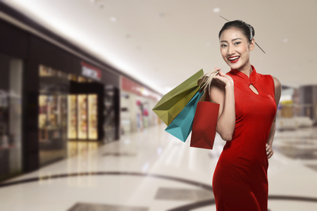 chicas de compras: Mujer china llevaba ropas tradicionales que sostienen la bolsa de compras con el fondo de la alameda Foto de archivo