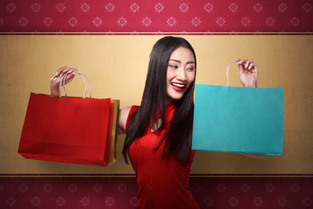 chicas comprando: Mujer china en la bolsa de la compra celebraci�n del cheongsam del vestido. Chino concepto nuevo a�o la venta