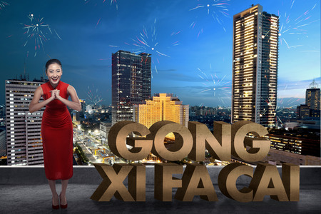 gong xi fa cai: Chinese woman in cheongsam dress smile. Happy chinese new year concept