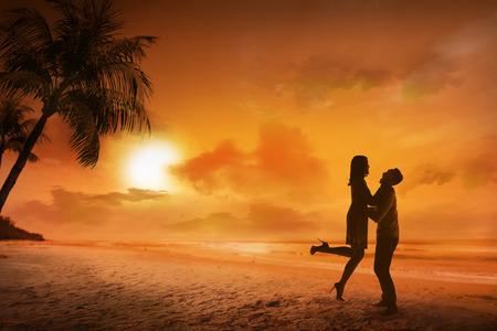 luna de miel: silueta de pareja joven en una playa en el fondo la puesta del sol Foto de archivo