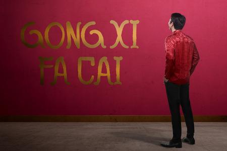 gong xi fa cai: Chinese man looking gong xi fa cai writing. Happy chinese new year concept