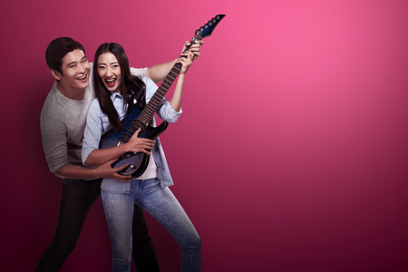 asian adult: Lovely asian couple playing guitar. Valentine day concept Stock Photo