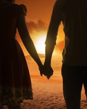 manos agarrando: silueta de pareja joven en una playa en el fondo la puesta del sol Foto de archivo