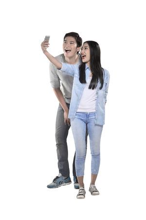 Aziatische paar doen selfie met mobiele telefoon geïsoleerd op witte achtergrond