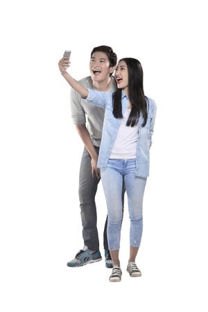 Asian couple doing selfie with cellphone isolated over white background