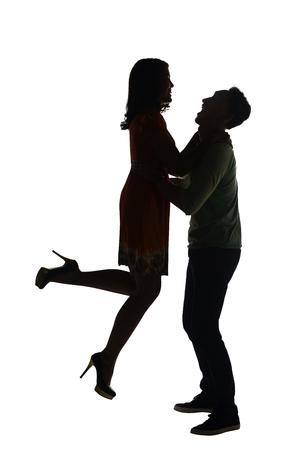 nene y nena: Silueta de la pareja mano que sostiene aislados sobre fondo blanco Foto de archivo