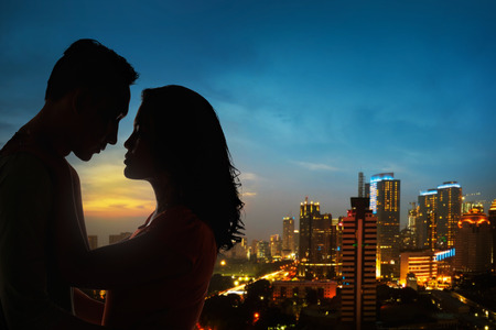 beautiful boy: Silhouette of couple on the rooftop in the night at the city Stock Photo