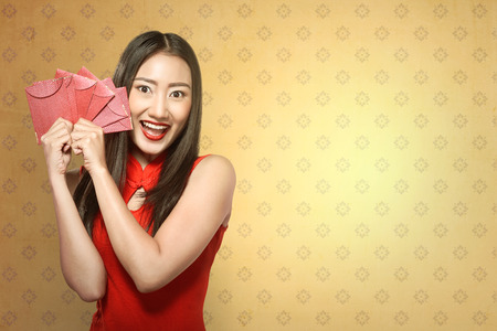 tradional: Chinese woman in tradional clothing holding angpao. Happy chinese new year concept Stock Photo