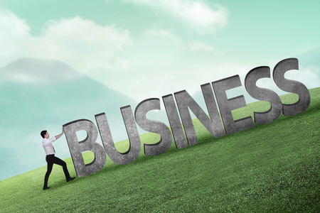 uphill: Asian business person pushing 3D business word uphill