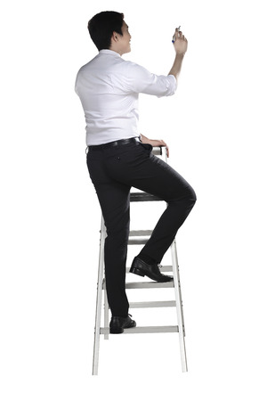Asian man write something with pen on the ladder isolated over white background