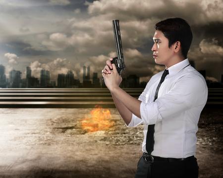 holding gun: Secret agent holding gun ready to fire Stock Photo