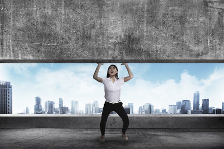 overburdened: Asian business woman lift heavy block. Business challenge concept