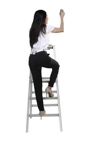 ladder: Asian woman write something with pen on the ladder isolated over white background Stock Photo