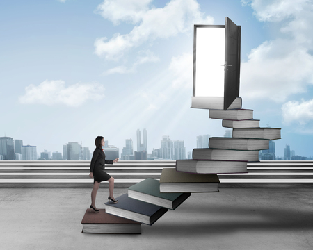 up stair: Asian business woman stepping up stair made from book. Business knowledge concept
