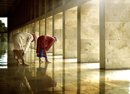 praying together: Two religious muslim man praying together inside the mosque
