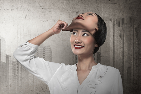 Asian business woman remove his other face mask. Changing mood concept Reklamní fotografie
