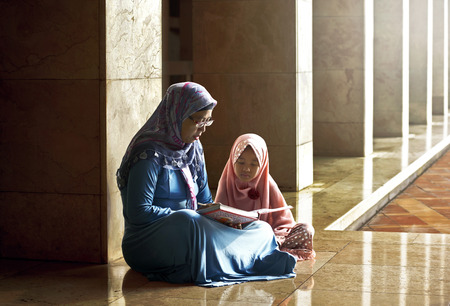 Muslim mother teach her daughter reading koran inside the mosque
