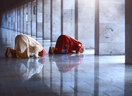 man praying: Two religious muslim man praying together inside the mosque