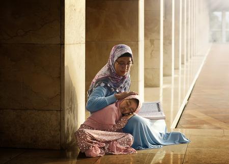 Muslimische Mutter ihre Tochter zu lesen koran in der Moschee lehren Standard-Bild - 52910335