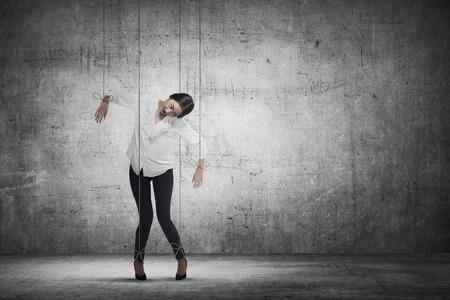 Aziatische zakenvrouw hace touwtje op haar lichaam als marionet. Zakelijke gemanipuleerd begrip