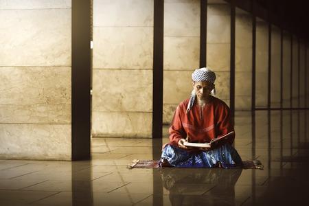 Religieuze moslim man lezing heilige koran in de moskee