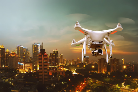 Small white drone flying over the city Stock Photo