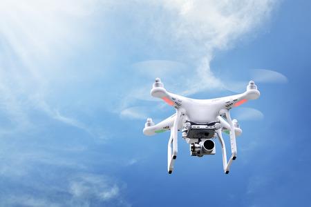 Mały biały Drone unosić z niebieskim tle nieba