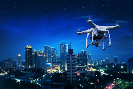 Pequeño avión no tripulado blanca volando sobre la ciudad Foto de archivo - 54229535