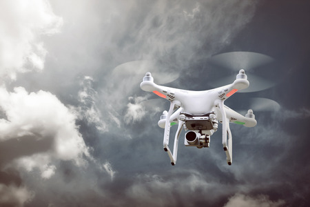 hover: Small white drone hover with blue sky background