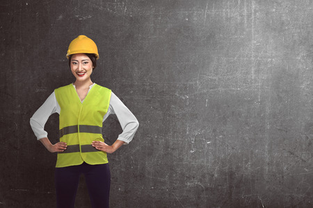 folding arms: Asian woman wear had hat and safety vest over grunge background Stock Photo