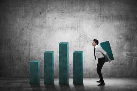 Asian business man carry heavy chart bar. Business development concept