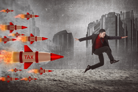oppressed: Asian business man jump from tax rocket. Tax escape concept