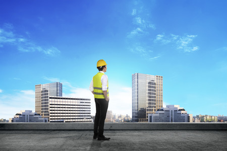 asian architect: Back view of young succesful asian architect over city background Stock Photo