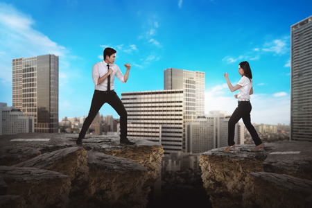 Business man and woman fighting on broken road