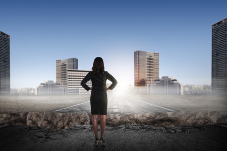 broken back: Back view of asian business woman looking the city from broken road Stock Photo