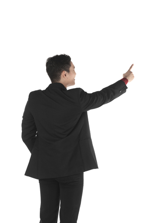 Asian business man pointing something isolated over white background Фото со стока